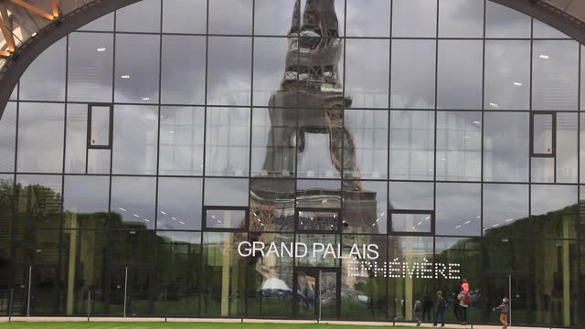 person is jogging on the champ de mars while the eiffel tower is reflected in the facade of the grand palais ephemereon may 10, 2021 in paris,... - grand palais stock videos & royalty-free footage