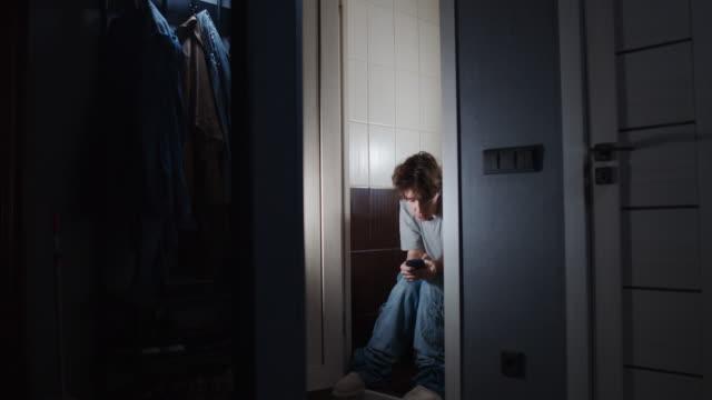 vídeos y material grabado en eventos de stock de la persona está sentada en el inodoro y usando el teléfono inteligente - domestic bathroom