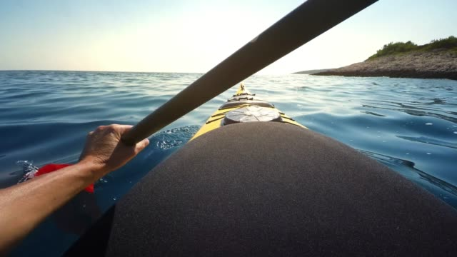 pov person kayaking at sea in sunshine - land stock videos & royalty-free footage