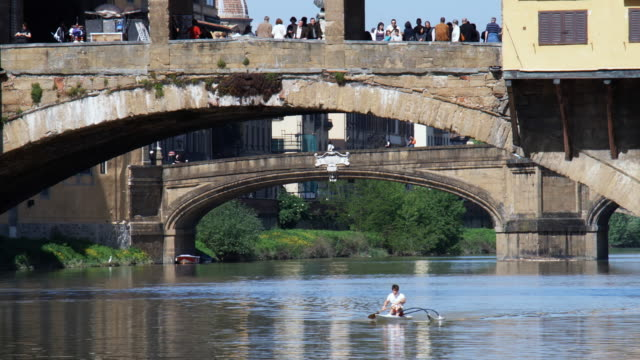 ws person kayaking underneath ponte vecchio, florence, tuscany, italy - tuscany stock videos and b-roll footage