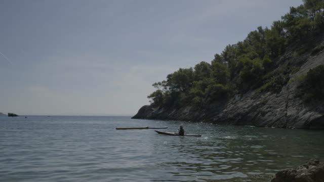 vídeos y material grabado en eventos de stock de person kayaks off hvar coastline, wide - cultura croata
