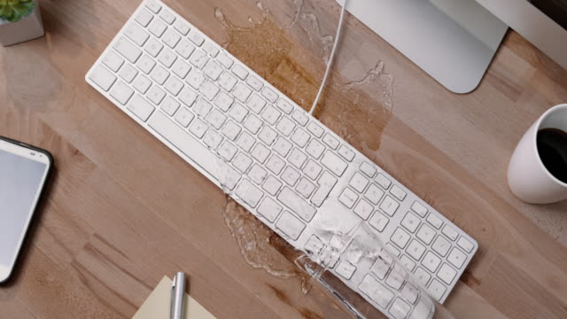 vídeos de stock e filmes b-roll de slo mo ld person knocking over a glass of water and spilling it on a white keyboard and mobile phone - teclado de computador
