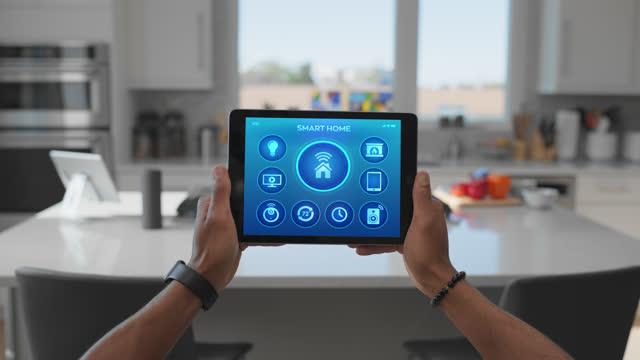 person lifts their tablet in the kitchen of their smart home - herunterlassen stock-videos und b-roll-filmmaterial