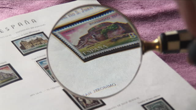 pov person looking at stamp collection through magnifying glass, bilbao, spain - postage stamp stock videos & royalty-free footage