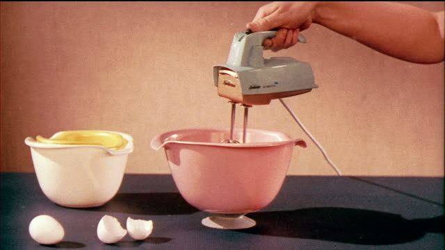 1958 MS Person lowering electric mixer into mixing bowl / USA / AUDIO