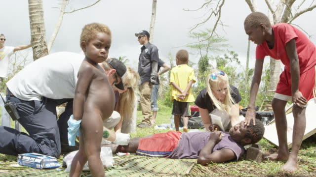 Vanuatu - March 31, 2015: Person lying on ground receives medical treatment for knee