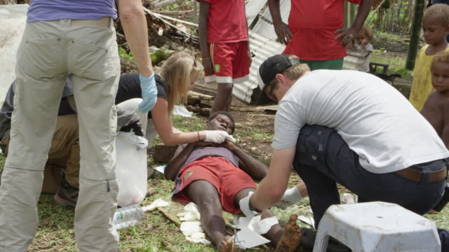 vanuatu - march 31, 2015: person lying on ground receives medical treatment for knee - rebuilding stock videos & royalty-free footage