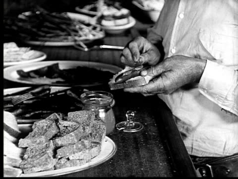 1924 b&w cu person making sausage sandwich  - hot dog stock videos & royalty-free footage