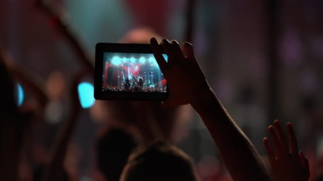 Person making smartphone video of a night concert