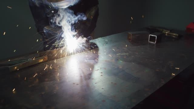 vídeos de stock, filmes e b-roll de uma solda mig da pessoa em uma tabela da soldadura do metal em uma oficina como faíscas voam - metal