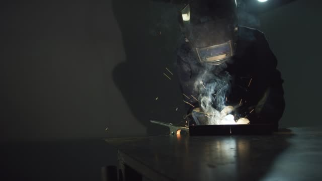 a person mig welds on a metal welding table in a workshop as sparks fly - repairman stock videos & royalty-free footage