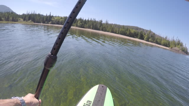 person navigates stand up paddle board on ocean bay - oar stock videos & royalty-free footage