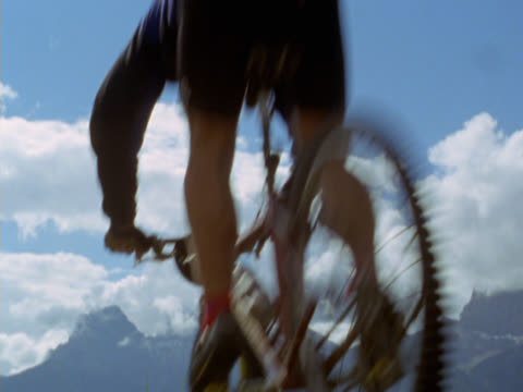 person on bike descending slope on mountain - mpeg videoformat stock-videos und b-roll-filmmaterial