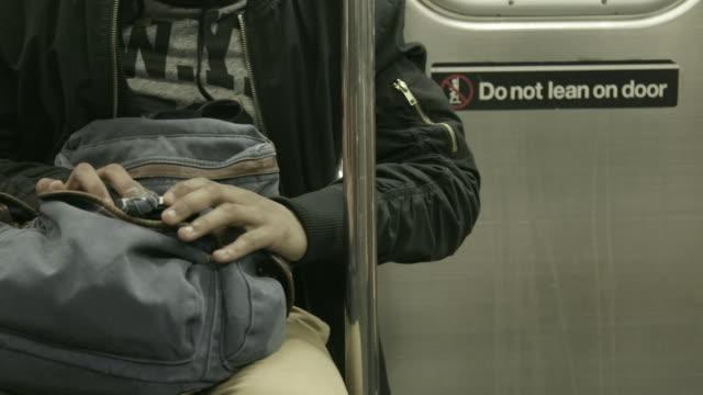 vídeos de stock e filmes b-roll de person on phone in subway car, close up - deslizar técnica de imagem