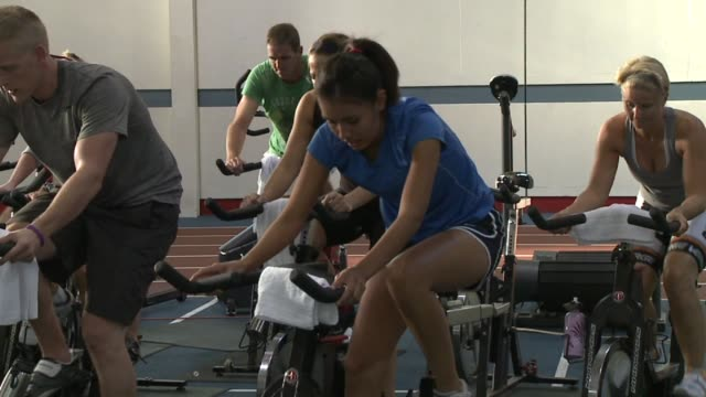 person on spin bike at national institute for fitness and sport on october 06, 2013 in indianapolis , indiana - インドアサイクリング点の映像素材/bロール