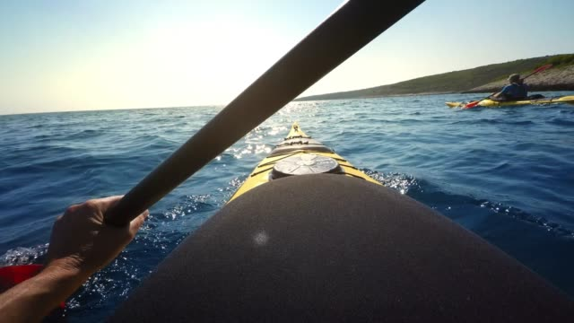pov person paddling a sea kayak in sunshine - pagaiare video stock e b–roll