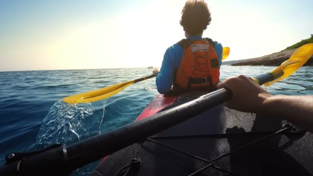 pov person paddling in a tandem sea kayak on a sunny day - kayak video stock e b–roll
