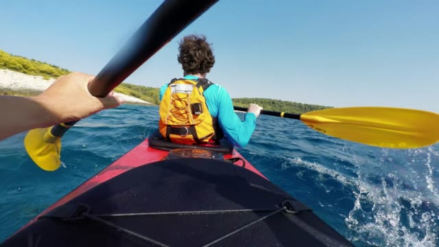pov person paddling in the back of a tandem sea kayak in sunshine - attività del fine settimana video stock e b–roll