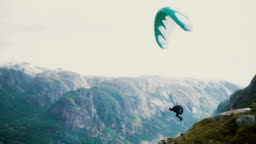 Person paragliding in mountains in Norway