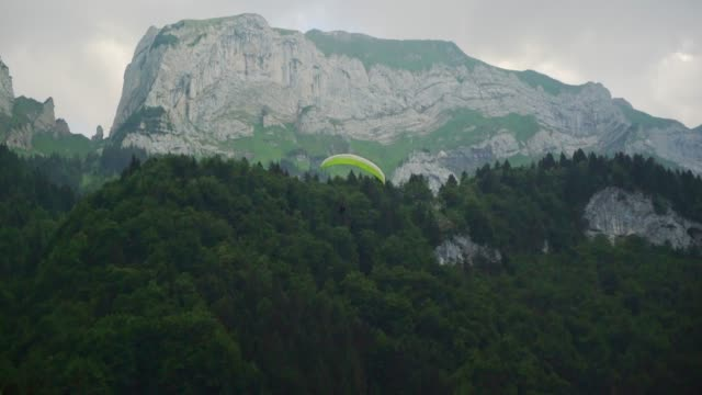 person paragliding in mountains in switzerland - paragliding stock videos & royalty-free footage