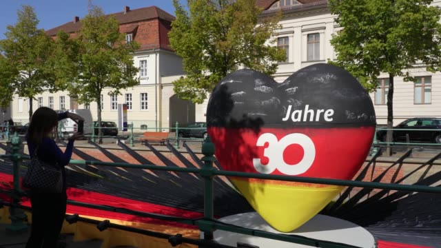 a person photographs a sculpture of a heart in the colors of the german flag that reads 30 years as part of an outdoor exhibition marking the... - 30 34 years stock videos & royalty-free footage