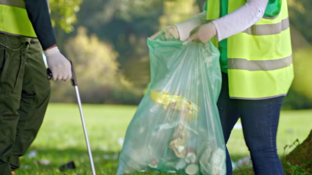 person picking up rubbish off the ground with a litter picker - bin bag stock videos & royalty-free footage