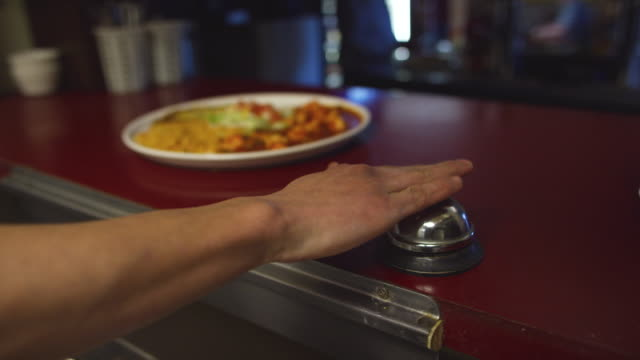 a person picks up a plate of hot mexican food and places it in a serving window and rings a bell for the server at a mexican restaurant - mexican restaurant stock videos & royalty-free footage