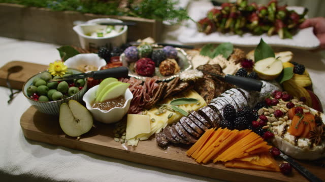 a person places an appetizer in the background while the camera pans an appetizer charcuterie meat/cheeseboard with various fruit, sauces, and garnishes on a table at an indoor celebration/party - french food stock videos and b-roll footage