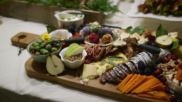 a person places an appetizer in the background while the camera pans an appetizer charcuterie meat/cheeseboard with various fruit, sauces, and garnishes on a table at an indoor celebration/party - putting stock videos & royalty-free footage