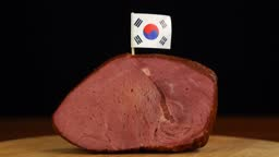 Person placing decorative Korean flag toothpicks into piece of red meat.