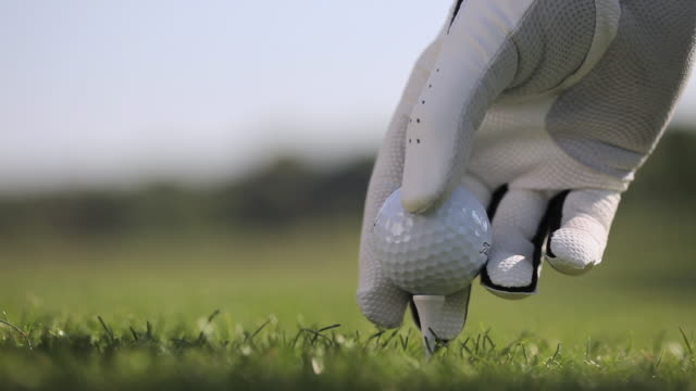 vidéos et rushes de cu person placing golf ball on tee and hitting / canterbury, kent, uk - balle de golf