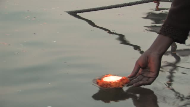 CU, Person placing Hindu votive candle (diya) onto Ganges rive, close-up of hand, Varanasi, Uttar Pradesh, India