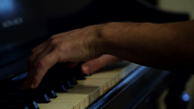 Person plays piano, close up