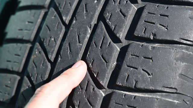 a person points with his index finger to a car tire worn out by time and use. - index finger stock videos & royalty-free footage