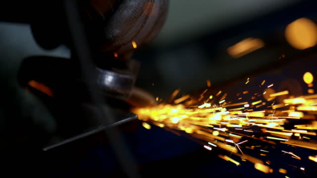 SLO MO Person polishing metal with an angle grinder