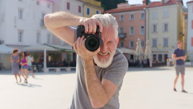 pov person posing for a male photographer with a grey beard taking photos in a town square - facial hair stock videos & royalty-free footage