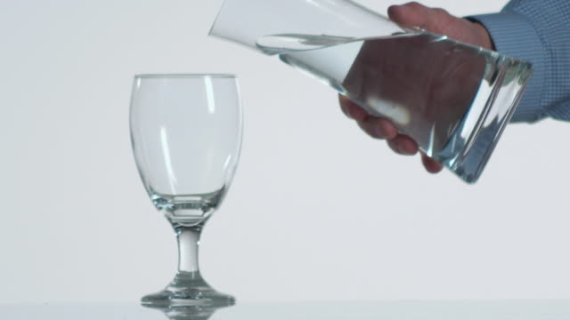 CU SLO MO Person pouring water from glass to another glass / Orem, Utah, USA