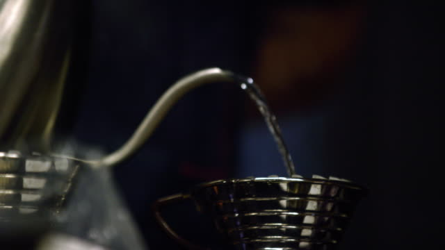 a person pours hot water from a metal teakettle's spout into the top of a metal pour-over coffee maker against a black background - pour spout stock videos & royalty-free footage