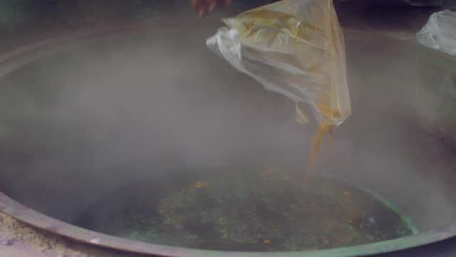 person pours yellow dye powder into steaming pot - silk stock videos & royalty-free footage