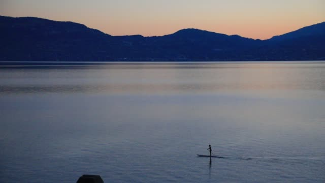 person practices standup paddleboarding during sunrise behind the alps on lake geneva on lake geneva on august 9, 2020 in saint gingolph,... - one person stock videos & royalty-free footage