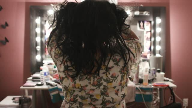 vidéos et rushes de person prepares for drag show, puts on wig in slow motion - virus hiv