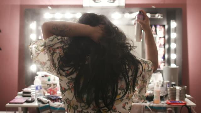 stockvideo's en b-roll-footage met person prepares for drag show, sprays wig in slow motion - pruik