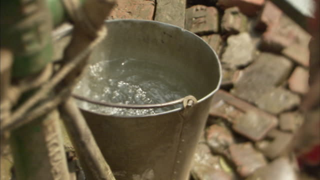 cu, ha, person pumping water into bucket outdoors, mawna, bangladesh - vattenpump bildbanksvideor och videomaterial från bakom kulisserna