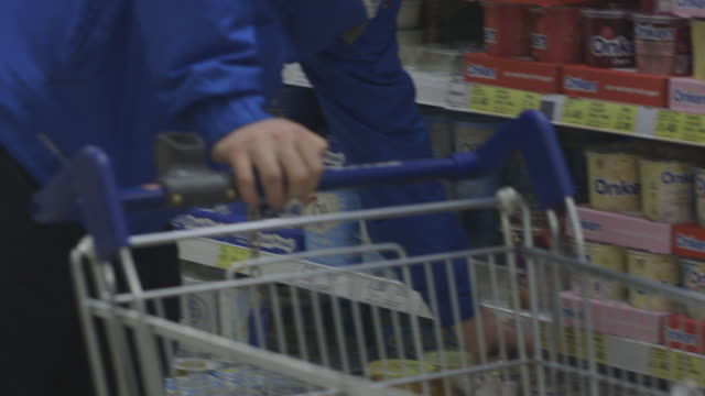 A person pushing a shopping trolley chooses yoghurt at a large UK supermarket.
