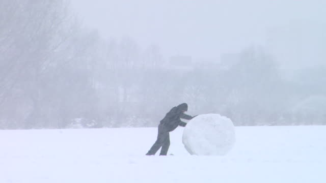 WS person pushing large snowball in field in a snowy Victoria Park, London