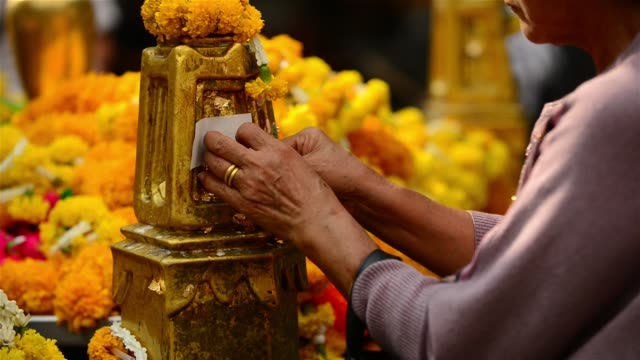 a person putting gold leaves offering on to the post at erawan shrine - gold leaf stock videos & royalty-free footage