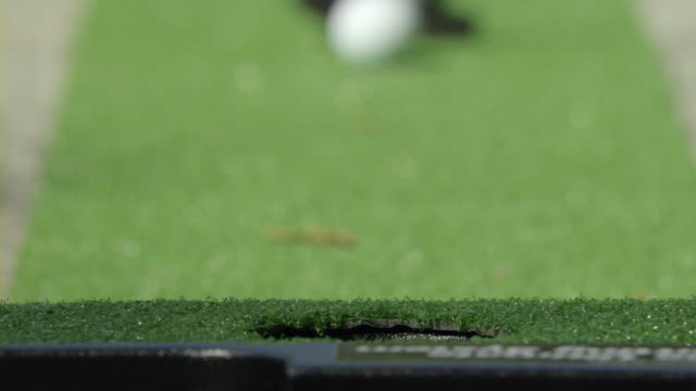 cu selective focus person putting golf ball into whole, encino, california, usa - minigolf stock-videos und b-roll-filmmaterial