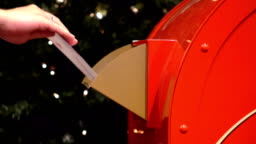 Person putting letter into mailbox for Santa Claus in slow motion