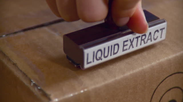 cu person putting 'liquid extract' stamp on package / burlington, vermont, usa - burlington vermont stock videos & royalty-free footage