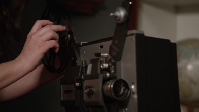 vídeos de stock, filmes e b-roll de person putting wheel on old projector - equipamento de projeção
